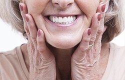 elderly lady touching her face and smiling