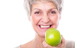 Woman with implant-retained dentures in Sachse holding an apple.