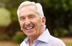 Older man with dental implant smiling.