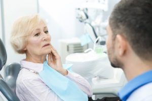 woman with mouth pain talking to her dentist about replacing her dentures in Sachse