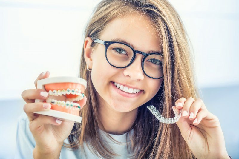 girl holding up braces and Invisalign